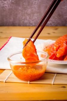 Salmone fresco raccolto con una bacchetta di legno e immerso in una ciotola di salsa di frutti di mare