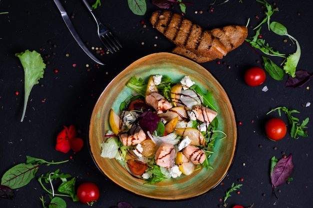 Insalata di salmone fresco con pera caramellata, feta e lattuga su una superficie scura