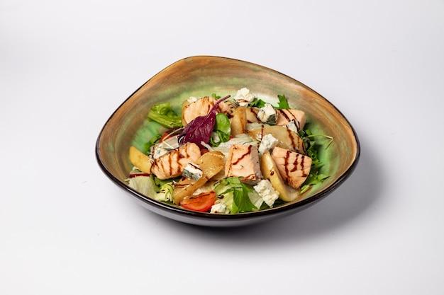 Insalata di salmone fresco con pera caramellata, feta e lattuga su una superficie bianca