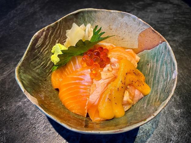 Scivolo di salmone fresco con ciotola di riso sul tavolo