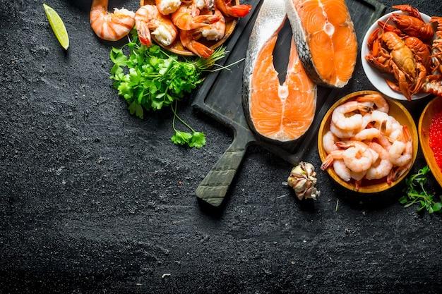 Trancio di salmone fresco su un tagliere con gamberetti, gamberi e prezzemolo. sul nero rustico