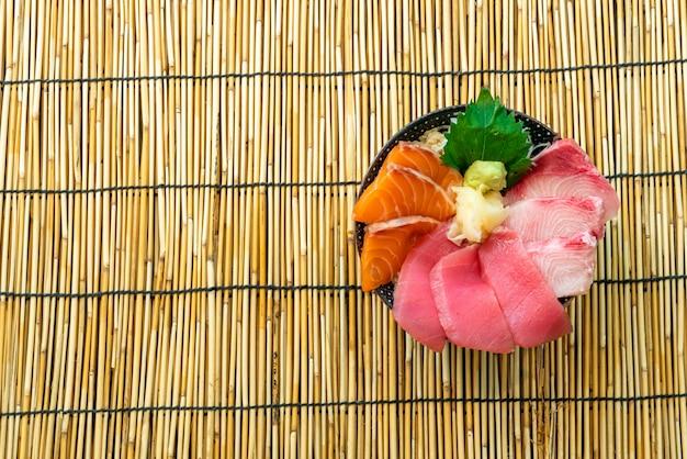 Tonno salmone fresco e hamachi crudo su riso ricoperto - stile di cibo giapponese