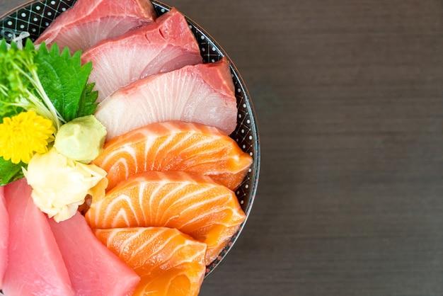 Salmone fresco, tonno e hamachi su una ciotola di riso ricoperta