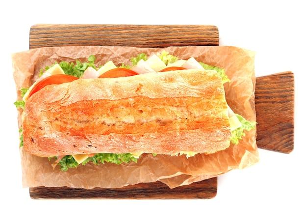 Panino fresco sul tagliere di legno isolato su bianco