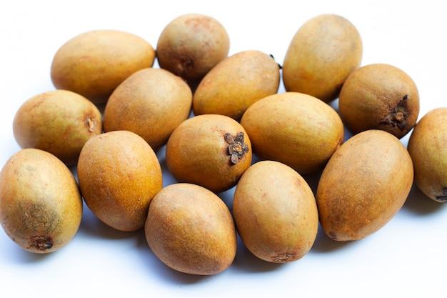 Frutta fresca di sapodilla isolata su fondo bianco.