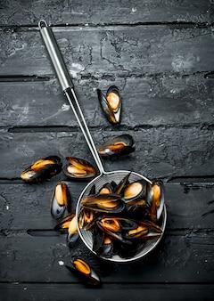 Vongole di pesce fresco in una casseruola. sul nero rustico.