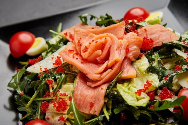 Insalata di mare fresca servita con salmone e caviale rosso