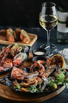 Frutti di mare freschi e vino bianco su un tavolo di pietra. ostriche, gamberi e capesante, calamari, serviti dallo chef, ben disposti su piatti, spazio di cemento scuro.
