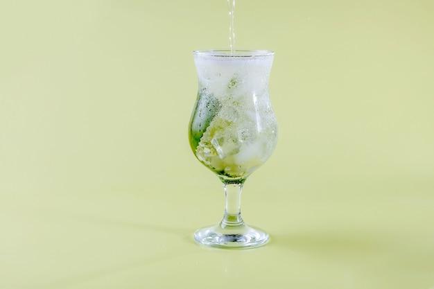 L'acqua fresca di seltz viene versata in un bicchiere con menta e ghiaccio