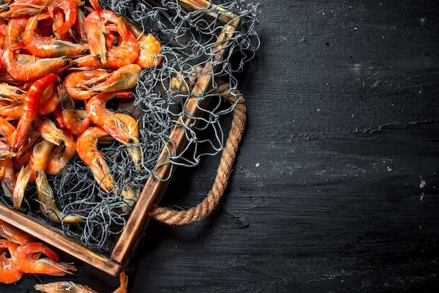 Gamberetti freschi in una rete da pesca su un vassoio sulla lavagna nera.