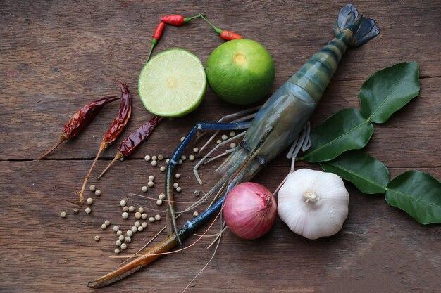Gamberi e ingredienti freschi con il limone per il pasto asiatico di tom yum goong su fondo di legno