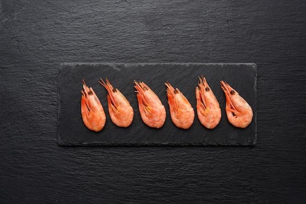 Gamberetti freschi di fila su una tavola di ardesia nera, vista dall'alto