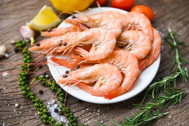 Il gamberetto fresco sul piatto bianco con gli ingredienti erba e spezie / cucinare i gamberetti dei gamberetti dei frutti di mare è servito su una tavola di legno