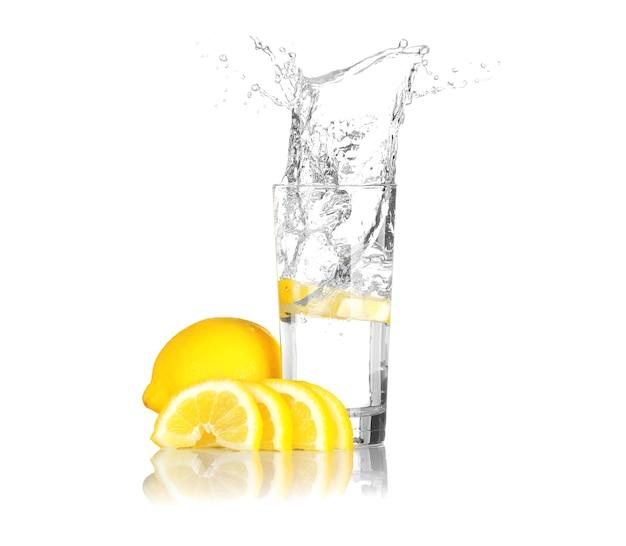 Fetta di limone fresca che cade nel bicchiere con acqua su priorità bassa bianca