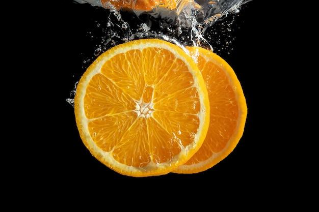 Frutta arancione affettata fresca nella spruzzata dell'acqua isolata sul nero.