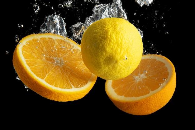 Arancia e limone affettati freschi nella spruzzata dell'acqua isolata sul nero.