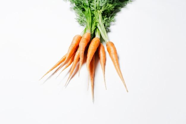 Piccole carote fresche isolate su fondo bianco, vista del primo piano.