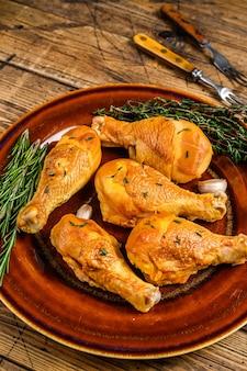 Cosce di pollo affumicate fresche su un piatto rustico con erbe aromatiche.