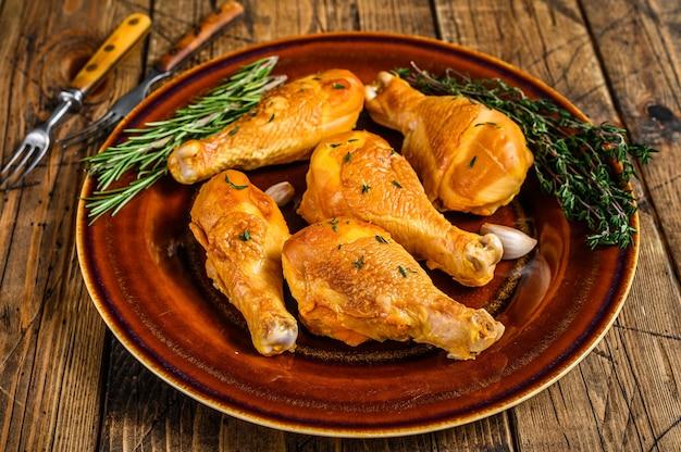 Cosce di pollo affumicate fresche su un piatto rustico con erbe aromatiche