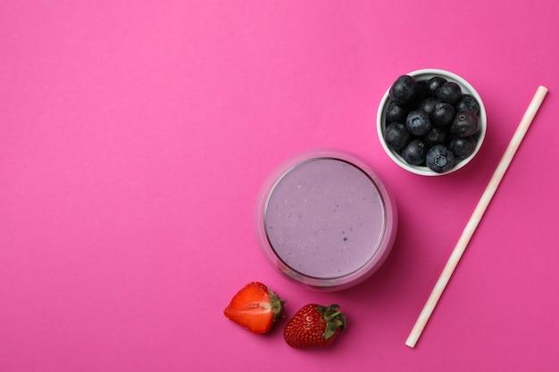 Frullato fresco, ingredienti e paglia su sfondo rosa