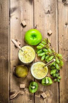 Frullato fresco con uva, mela e kiwi. su uno sfondo di legno.