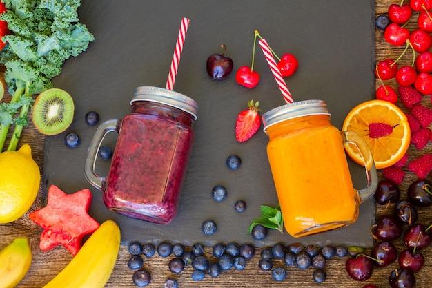 Frutti di bosco freschi frullati e bevanda salutare arancia in barattoli di vetro con ingredienti