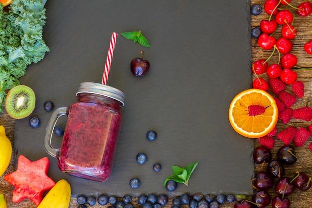 Frullato di bacche fresche bevanda salutare in un barattolo di vetro con ingredienti