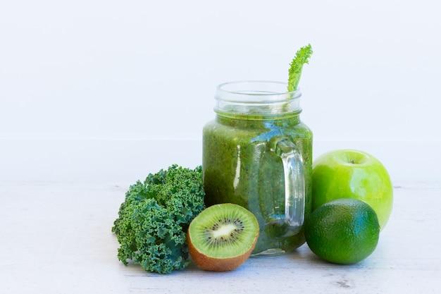 Bevanda salutare verde frullato fresco in un barattolo di vetro con ingredienti