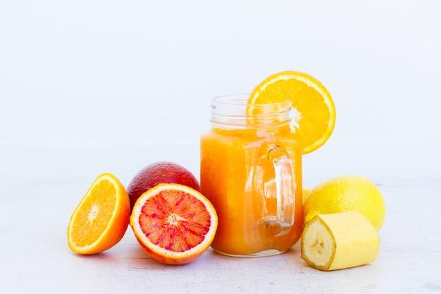 Bevanda salutare arancia frullata fresca in barattoli di vetro con ingredienti