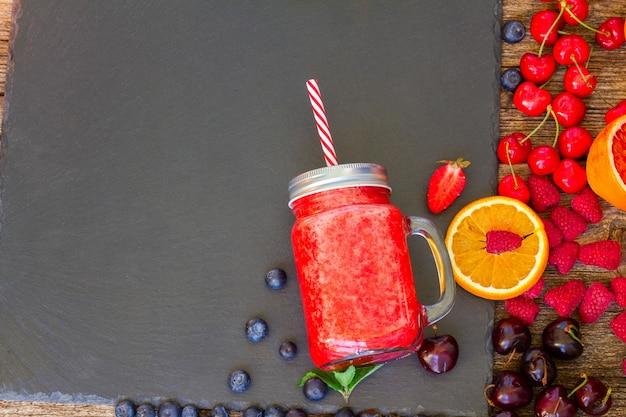 Bevanda rossa frullata fresca in un barattolo di vetro con ingredienti sul nero