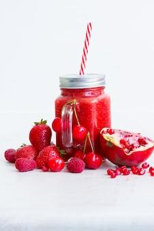 Bevanda rossa frullata fresca in barattoli di vetro con ingredienti