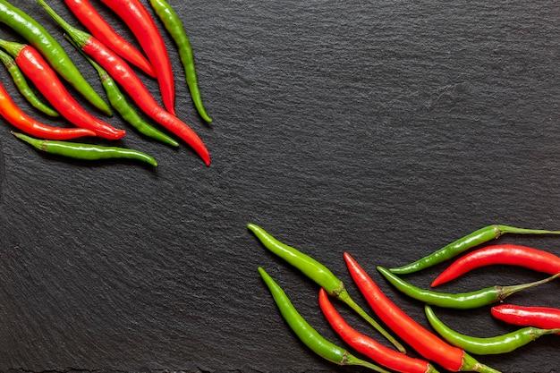Pepe rosso e verde piccante fresco su una tavola di ardesia, vari peperoncini colorati e peperoni di caienna su sfondo scuro dall'alto. vista dall'alto, copia dello spazio.