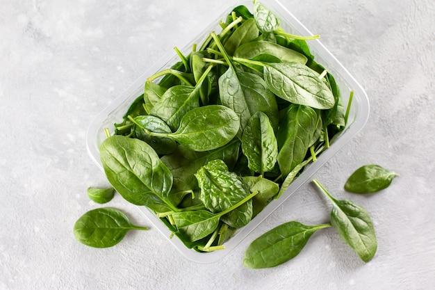 Foglie fresche di spinaci. spinaci crudi per insalata o frullato vegetariano o vegano su uno sfondo grigio cemento. vista dall'alto, copia dello spazio.