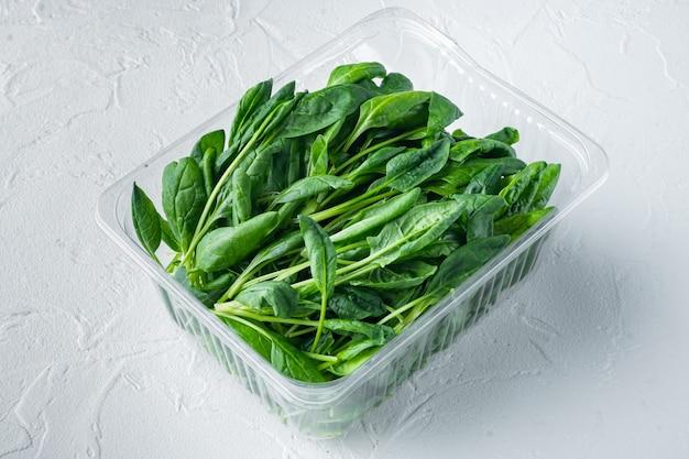 Set di spinaci freschi, su sfondo bianco, in confezione di plastica