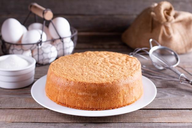 Pan di spagna fresco su un piatto bianco su un tavolo di legno. biscotto in chiffon per torta, fuoco selettivo