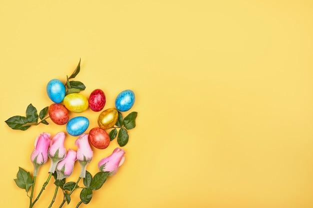 Fiori freschi di primavera e uova di pasqua colorate su sfondo giallo con spazio di copia. sfondo di pasqua con uova festive decorate