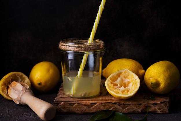Spremuta fresca dalle metà del limone con uno spremiagrumi in un barattolo di vetro, fuoco selettivo
