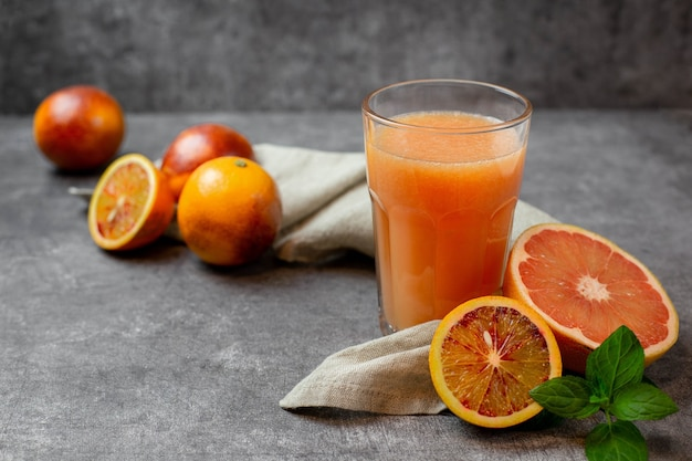 Spremuta fresca con pompelmo e frutti di arancia rossa su una superficie di cemento grigio scuro