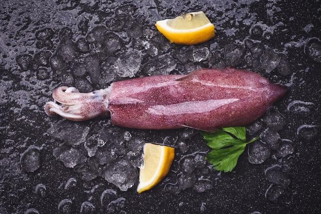 Calamari freschi polpo o seppia per cibo cotto ristorante di insalata, calamari crudi su ghiaccio con prezzemolo al limone sul mercato dei frutti di mare piatto scuro