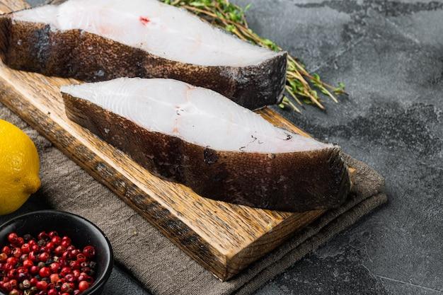 Set di halibut di pesce crudo di bistecca fresca, con ingredienti ed erbe di rosmarino, su tavola di pietra grigia