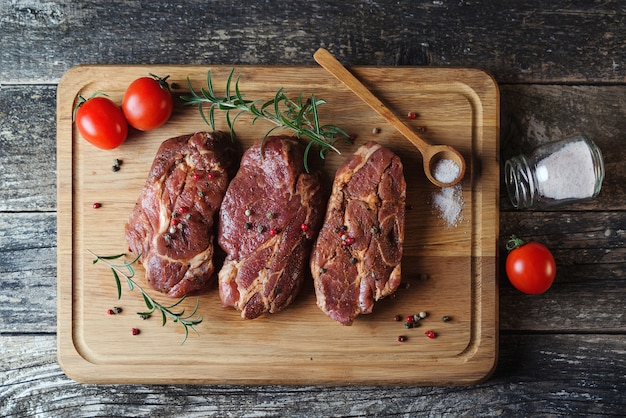 Bistecche fresche su tavola di legno, vista dall'alto. carne di maiale cruda. maiale fresco con ingredienti per cucinare. bistecca di gonna su tagliere di legno con erbe e pomodori.