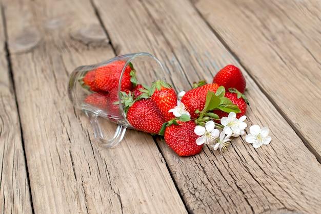 Fragole fresche in una tazza di vetro su una tavola di legno