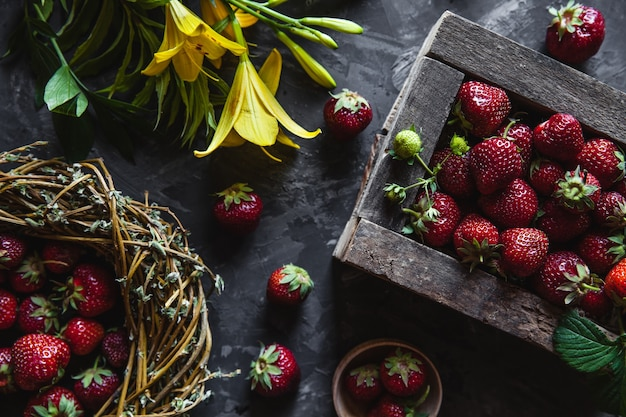 Fragole fresche in una vecchia scatola su una superficie grigia con fiori gialli. cibo sano, frutta