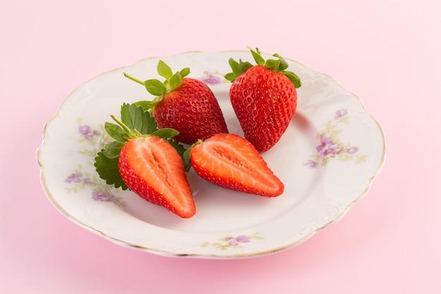 Fragole fresche sul vecchio piatto su backround rosa
