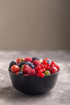 Fragola fresca, mora, uva spina, lampone e mirtillo in una ciotola nera con grigio.