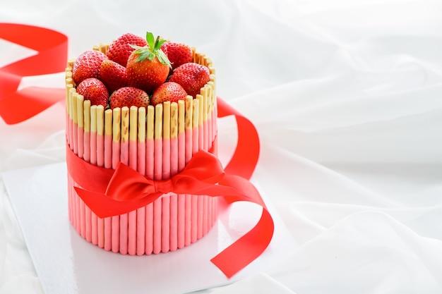 Torta di fragole fresca con bastoncini di biscotto alla fragola e nastro rosso sul panno bianco
