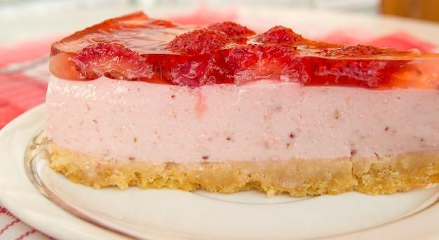Cheesecake alla fragola fresca, un pezzo con strati, vista laterale, primo piano