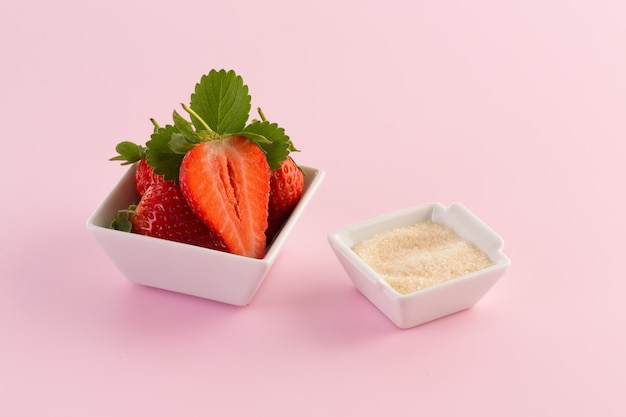 Fragola e zucchero freschi su backround rosa