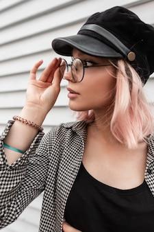 Fresco ed elegante ritratto di moda bella ragazza con i capelli rosa in occhiali vintage e un cappello con una camicia a quadri casual cammina per strada vicino a un muro di legno in legno