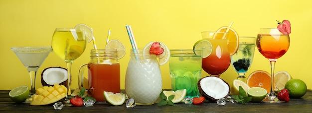 Cocktail estivi freschi sul tavolo di legno su sfondo giallo